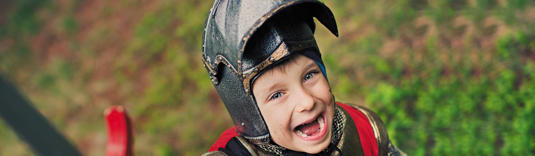 Kids go free image - young boy wearing a Knight's costume