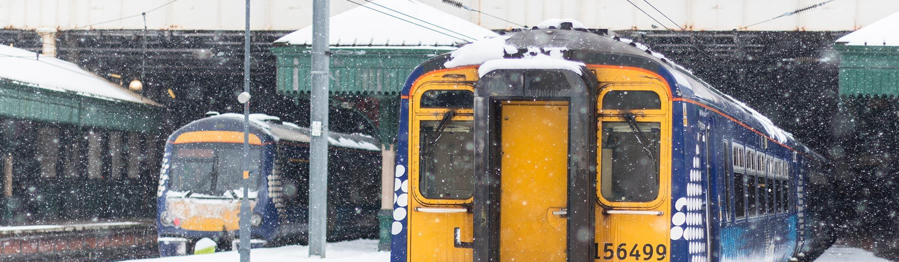 Snow on trains at a station
