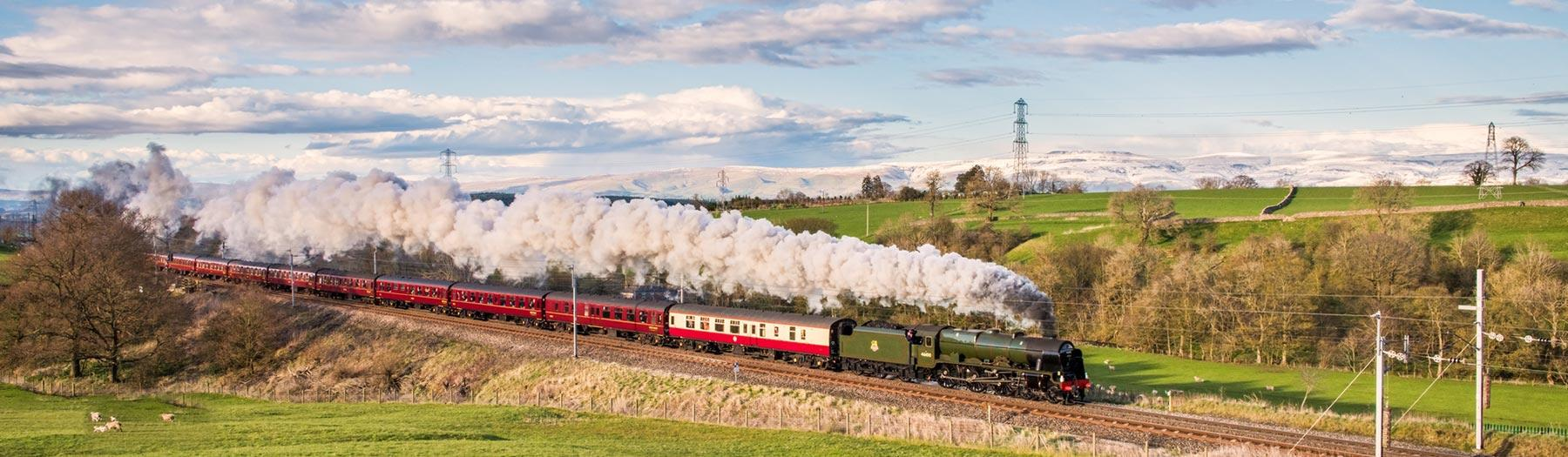 Royal Scot steam locomotive and vintage carriages passing through fields